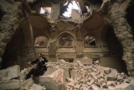 sarajevo-1992-durante-la-guerra-nella-biblioteca-nazionale-parzialmente-distrutta-il-musicista-il-violoncellista-locale-vedran-smailovimikhail-evstafiev